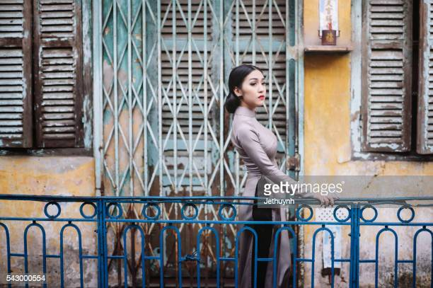 Woman wearing Aodai standing in an ancient town, China Town, Saigon