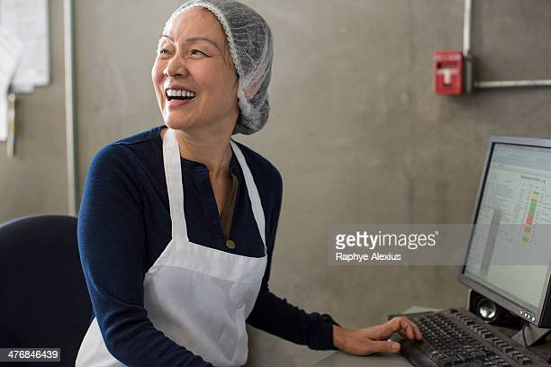Woman wearing apron and hairnet using computer