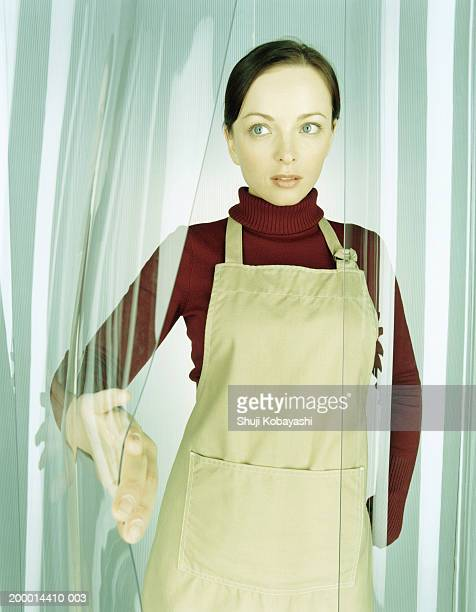 Woman wearing apron, holding open plastic curtain