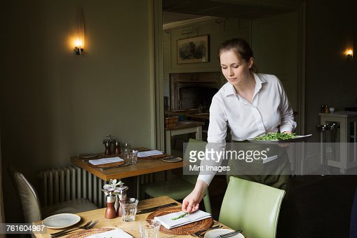 Woman wearing apron setting table in a restaurant.
