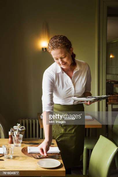 woman wearing apron setting table in a restaurant. - waitress stock pictures, royalty-free photos & images