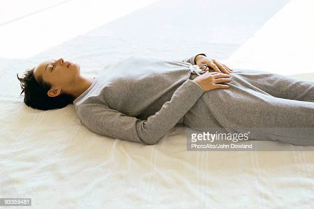 woman wearing athletic wear lying on back with hands placed on lower abdomen - hands in her pants fotografías e imágenes de stock