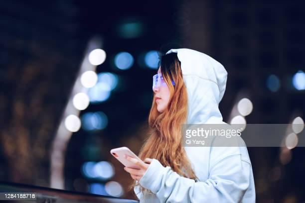 woman wearing augmented reality glasses using mobile phone on the street - hud interfaccia grafica utente foto e immagini stock