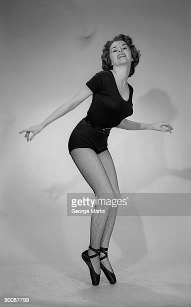 Woman wearing ballet leotard standing on tiptoes, studio shot