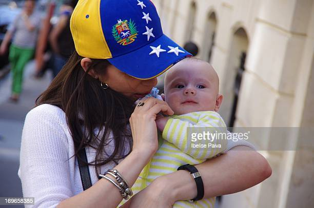 Woman wearing baseball cap with Venezuela's flag colors holds baby while waiting to vote at the Venezuelan presidential elections. Venezuela's...