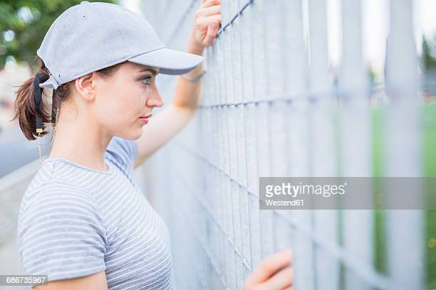 Woman wearing basecap looking through fence