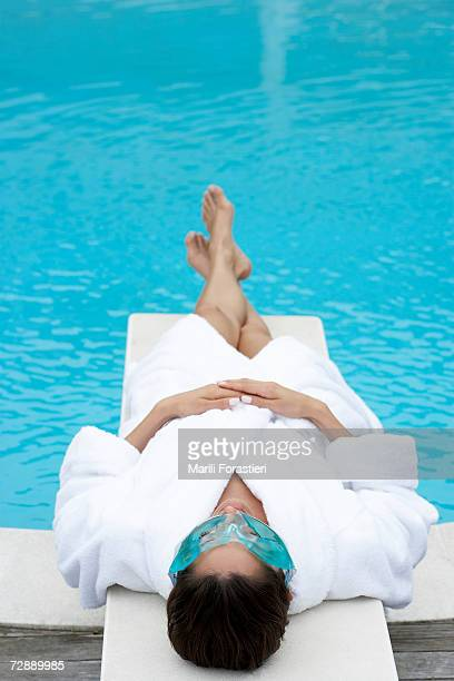 Woman wearing bathrobe and facial mask lying on springboard, elevated view