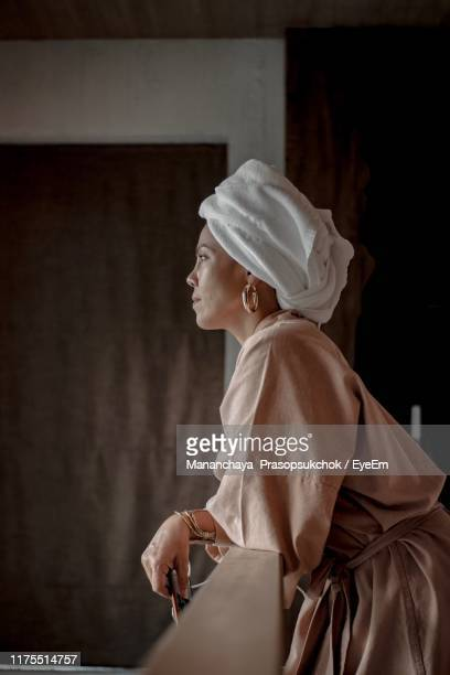 woman wearing bathrobe and looking away while standing by railing at home - bathrobe stock pictures, royalty-free photos & images