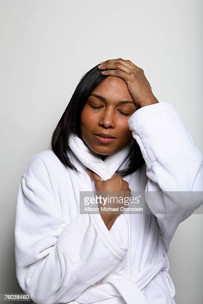 woman wearing bathrobe holding hand on head - allison michael orenstein stock pictures, royalty-free photos & images