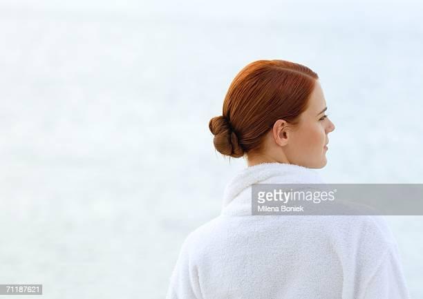 Woman wearing bathrobe, overlooking sea, rear view