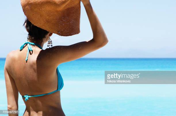 woman wearing bikini and holding sun hat while standing on beach - islas griegas fotografías e imágenes de stock