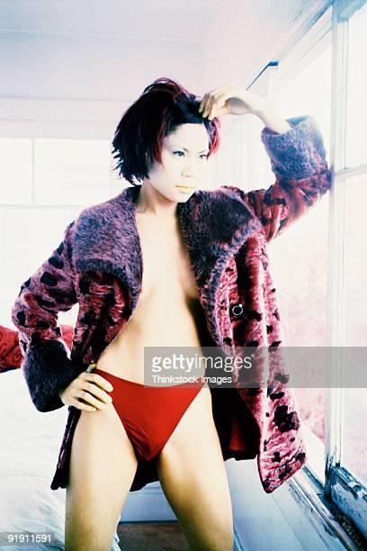 Woman wearing bikini bottom and faux fur jacket, standing by window, hand to head