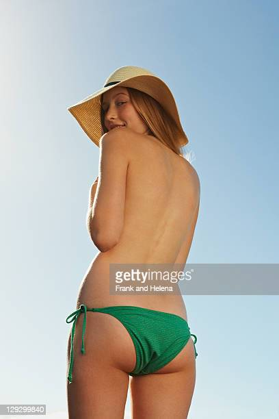 Woman wearing bikini bottoms and hat
