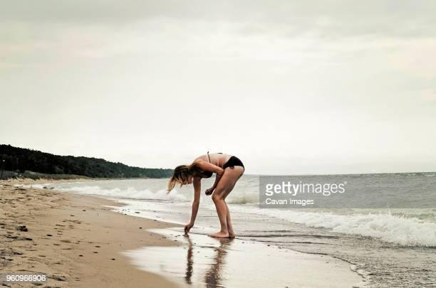 Woman wearing bikini collecting seashells at beach against clear sky