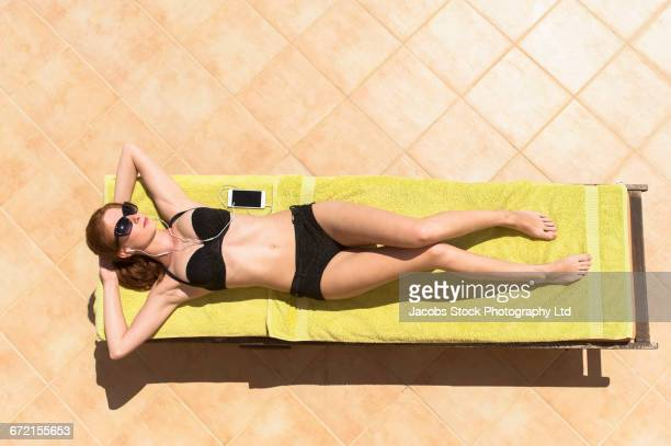 Woman wearing bikini laying on deck chair listening to cell phone