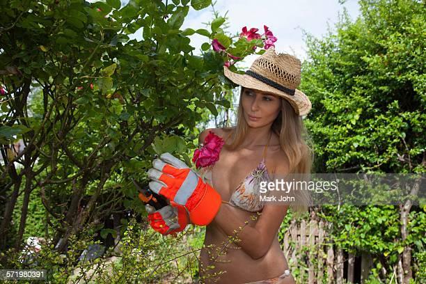 Woman wearing bikini pruning tree in garden