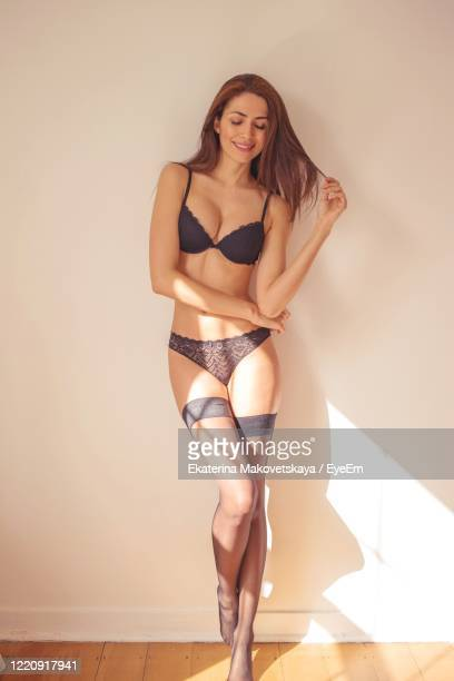 woman wearing bikini standing against wall - black stockings stock pictures, royalty-free photos & images