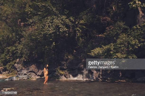 woman wearing bikini standing in river at forest - fabrizio zampetti foto e immagini stock