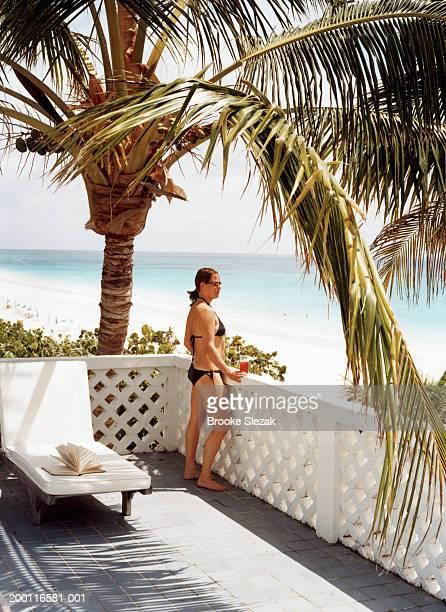 Woman wearing bikini, standing on balcony overlooking beach