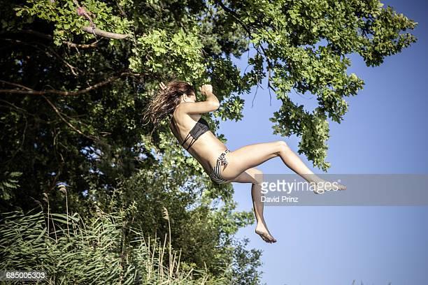 Woman wearing bikini swimming on tree swing