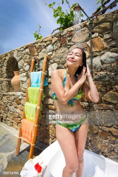 woman wearing bikini under outdoor shower - frau unter dusche stock-fotos und bilder