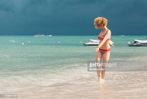 Woman Wearing Bikini Walking On Shore At Beach