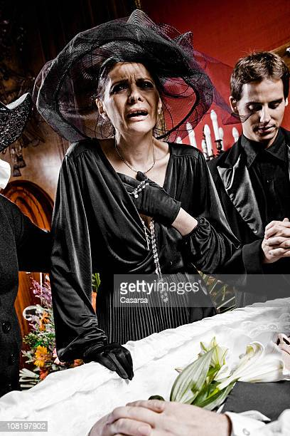 Woman Wearing Black and Crying Over Coffin