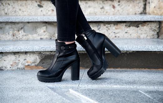 Woman wearing black boots 990211696