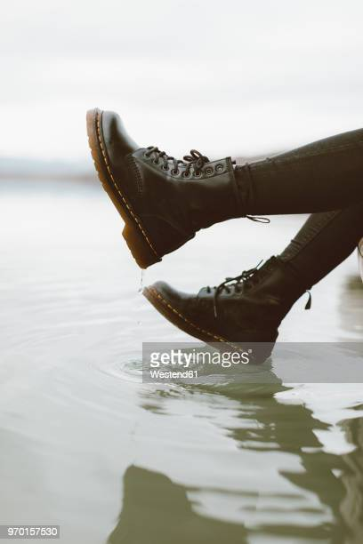 woman wearing black boots touching water surface of lake, partial view - bottes en cuir photos et images de collection