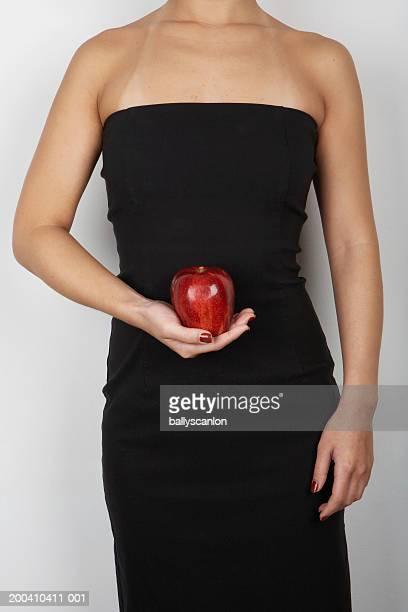 woman wearing black dress and holding apple - marque de bronzage photos et images de collection