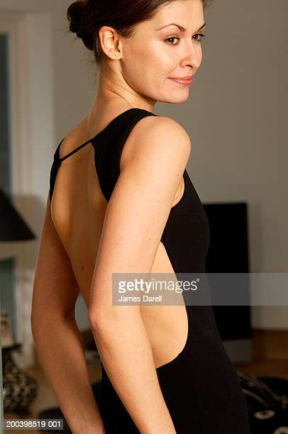 woman wearing black dress, looking over shoulder - cocktail dress stock pictures, royalty-free photos & images