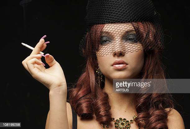 woman wearing black veil and hat smoking - beautiful women smoking cigarettes stock pictures, royalty-free photos & images
