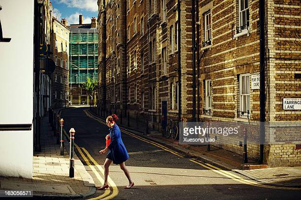 Woman wearing blue coat, walking pass narrow street in London, Farringdon Lane