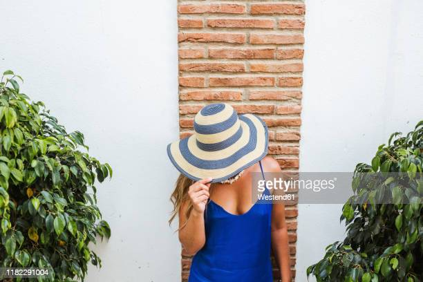 woman wearing blue dress and straw hat standing in front of wall, nerja, spain - striped dress stock pictures, royalty-free photos & images