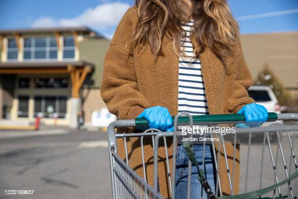 a woman wearing blue latex gloves and pushing a shopping cart during the covid-19 quarantine. - surgical glove stock pictures, royalty-free photos & images