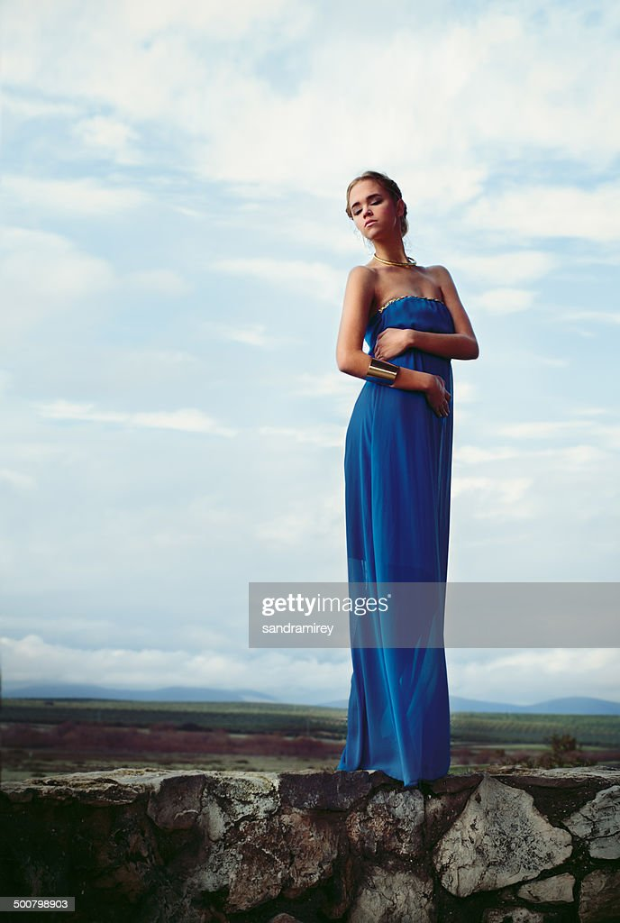 Woman wearing blue long dress standing on stone wall : Stock Photo