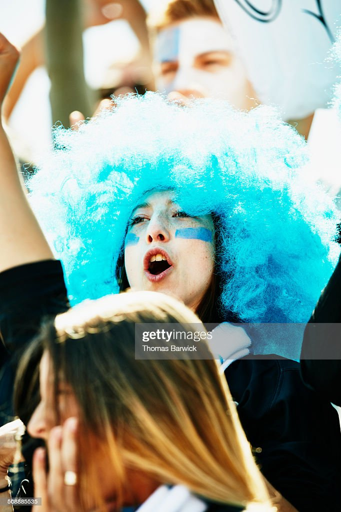 Woman wearing blue wig yelling during soccer match : Stock Photo