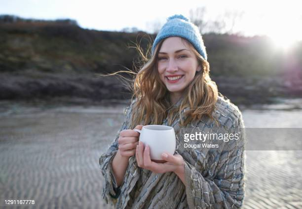 woman wearing bobble hat on winter beach with hot drink. - low tide stock pictures, royalty-free photos & images