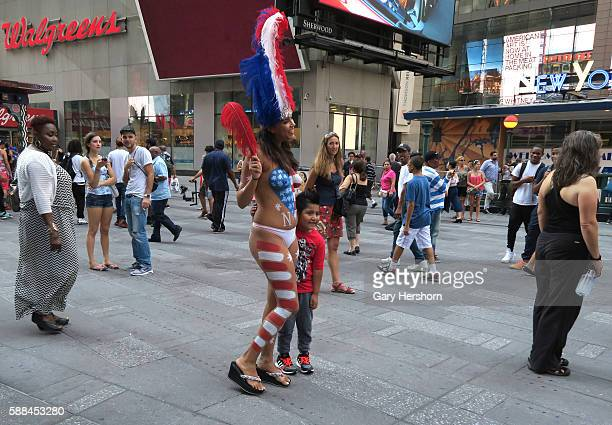 A woman wearing body paint poses for a picture in Times Square in New York August 18 2015