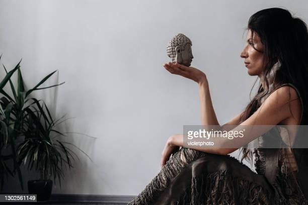 a woman wearing bohemian style dress practicing meditation with buddha statue - ceremony stock pictures, royalty-free photos & images