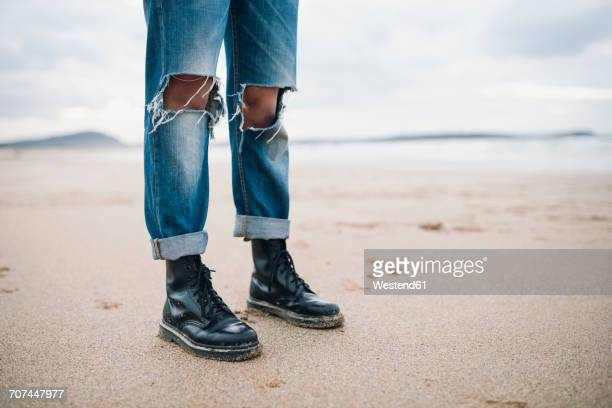 woman wearing boots and torn jeans on the beach, partial view - laars stockfoto's en -beelden