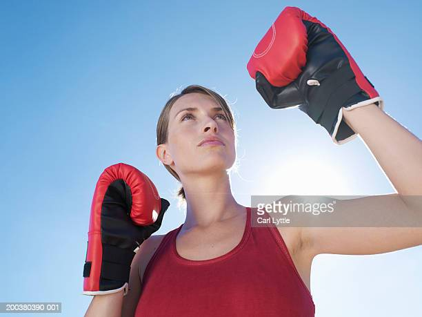 Woman wearing boxing gloves, low angle view (sun flare)