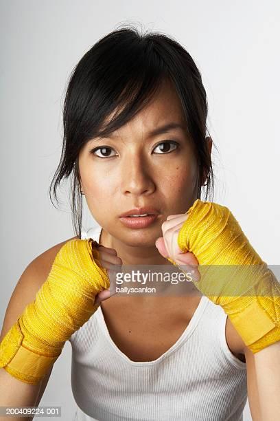 Woman wearing boxing wraps, portrait