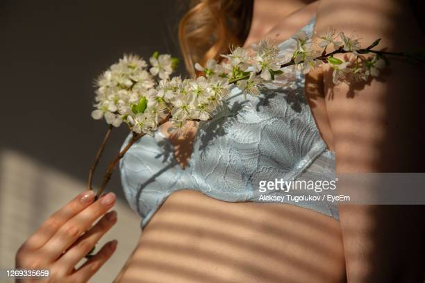 woman wearing bra holding flowers in darkroom - bras stock pictures, royalty-free photos & images