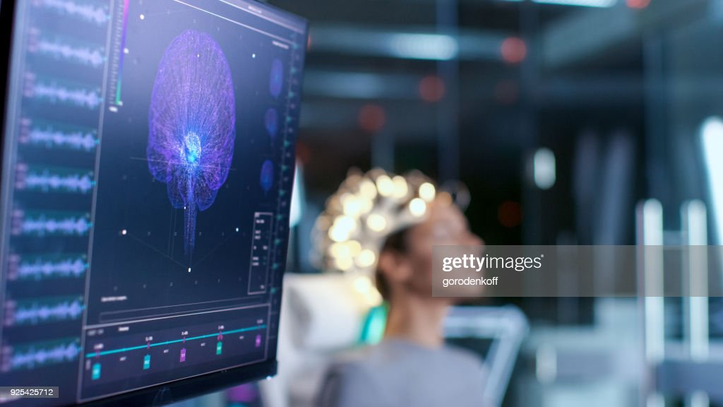 Woman Wearing Brainwave Scanning Headset Sits in a Chair In the Modern Brain Study Laboratory/ Neurological Research Center. Monitors Show EEG Reading and Brain Model. : Stock Photo