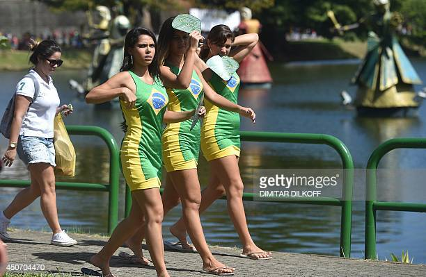Woman wearing Brazil dresses are seen prior to the Group G football match between Germany and Portugal at the Fonte Nova Arena in Salvador during the...