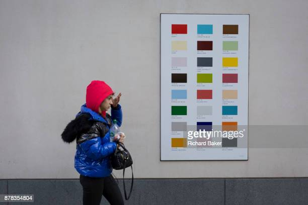 A woman wearing bright blue and red walks past a colour swatch on the wall of a central London business on 22nd November 2017 in London England