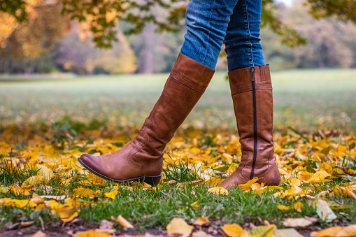 Woman wearing brown leather boot and walking in fallen leaves. 1062557898