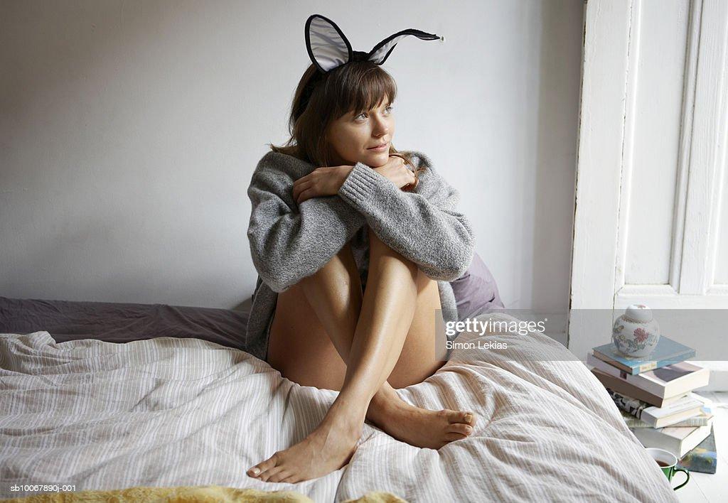 Woman wearing bunny ears sitting on bed, hugging knees, looking away : Stock Photo