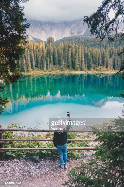 woman wearing bunny ears wig at carezza lake in italy - easter vacation concept - italian easter stock pictures, royalty-free photos & images